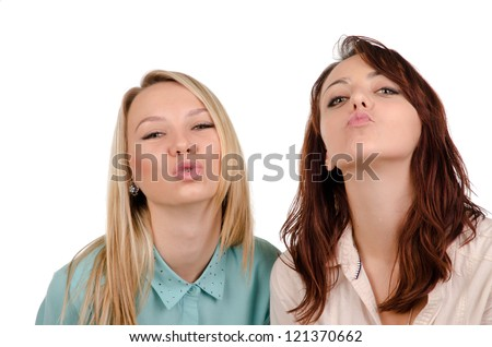 Two playful sexy girls begging for a kiss with their lips puckered and their heads tilted back isolated on white