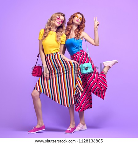 Two Playful Sisters Friends Having Fun in Studio on Purple. Young Beautiful Model Woman with Blowing lips Expression in Striped Fashion Trendy Outfit. Full-length portrait Crazy Girls