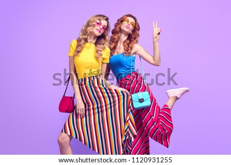 Two Playful Sisters Twins with Kiss Face Expression. Young Beautiful Girl Having Fun in Studio on Purple. Model Woman in Stylish Sunglasses, Striped Fashion Trendy Outfit. #1120931255