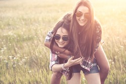 Two playful young women having fun outdoors at sunset light. Toned. High Key