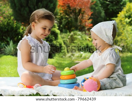 Two playing little sisters in the summer garden - stock photo