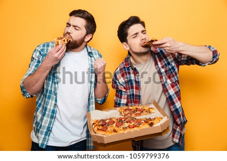 Two pleased men in shirt eating pizza and looking at the camera over yellow background