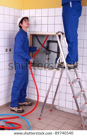 Two plumber fixing bathroom water supply