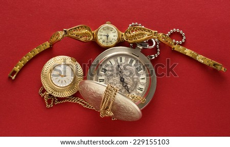 Two pocket watches and hand watch on red