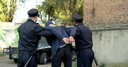 Two Police Officer Arresting Young Man. Police enforcement concept.