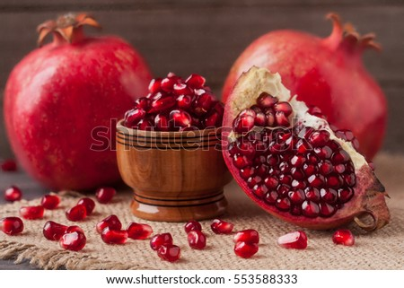 two pomegranate and grains in the bowl on the old wooden board with sackcloth #553588333
