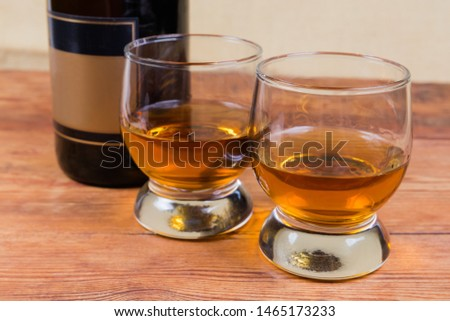 Two portions of brandy in brandy bowls on a background of brandy bottle on the rustic table in selective focus #1465173233