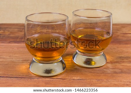 Two portions of brandy in brandy bowls on rustic table #1466223356