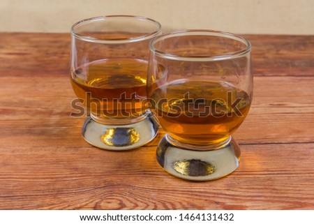 Two portions of brandy in brandy bowls on the rustic table #1464131432