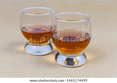 Two portions of brandy in brandy bowls on the tablecloth close-up #1465174499