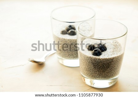 Two portions of chia pudding with vegan almond milk, blueberry, served in glasses. Healthy vegetarian breakfast, seeds, berries & greek yogurt, silver spoon. Background, copy space, close up, top view
