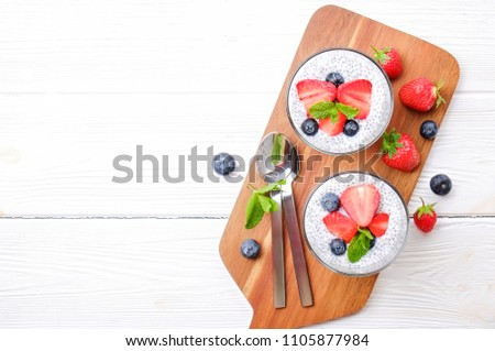 Two portions of chia pudding with vegan almond milk, blueberry & strawberry, mint, served in glasses. Healthy vegetarian breakfast, seeds, berries, greek yogurt, spoon. Background, close up, top view.