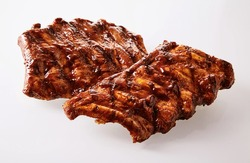 Two portions of delicious spicy marinated spare ribs barbecued over the grill over a white background