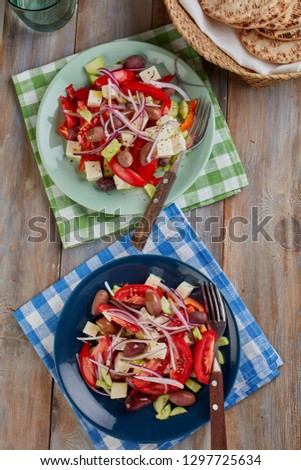 Two portions of Greek salad on a rustic table