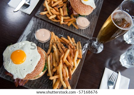 two portions of hamburger with fried egg on top and fries