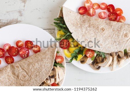 Two portions of healthy sandwiches with whole wheat wrap, chicken breast, mushroom, cherry tomatoes, parsley, arugula and yellow bell pepper. Balanced food
