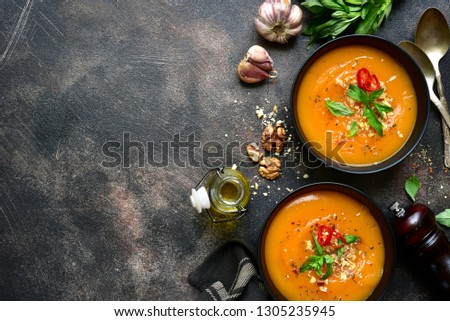 Two portions of homemade pumpkin carrot soup with walnuts in a black bowls over dark slate, stone or concrete background.Top view with copy space.