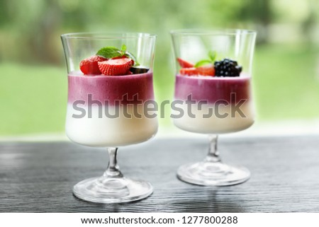 Two portions of sweet mousse with fresh berries and coulis in glasses