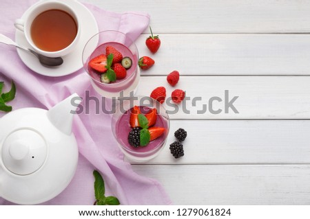 Two portions of sweet mousse with fresh berries and coulis in glasses, served with fresh tea, top view, copy space