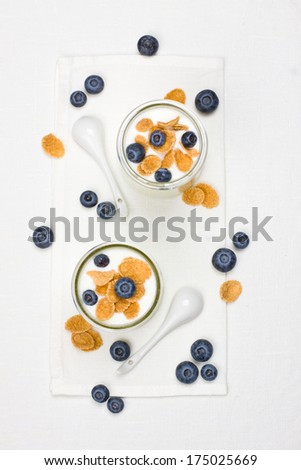 Two portions of yogurt with cornflakes and berries