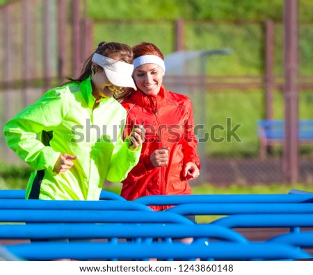 Two Positive and Smiling Caucasian Sportswomen in Outdoor Outfit Having Jogging Training Together. Training on Obstacle Course.Horizontal Image