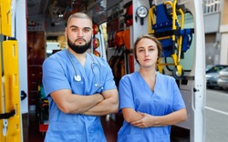 Two positive friendly  confident paramedicals in uniform posing near ambulance car