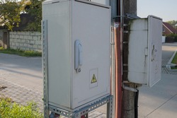 Two power distribution cabinets with voltage symbol on doors, mounted on pole and near pole on metal frame with wires passed through corrugated pipe, against background of suburban concrete road.