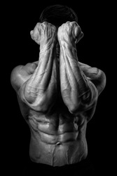 Two Power Mans Hands in Front of Face. Close-up of a man's fists and abs. Strong man's arm with muscles and veins. Black and white photo