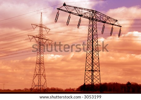 Two power poles in the sunset sky.