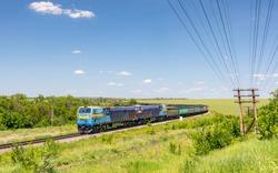 Two powerful diesel locomotives TE33AS pull a very long, heavy train of freight wagons along a winding single-track railway line. Summer shot. Ukrainian railways. Wide eye.
