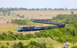 Two powerful diesel locomotives TE33AS pull a very long, heavy train of freight wagons along a winding single-track railway line. Summer shot. Large zoom. Ukrainian railways.