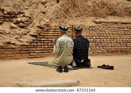 Two praying men from back