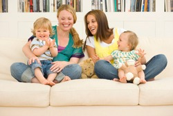 Two pregnant mothers on sofa at home with toddler son and baby girl