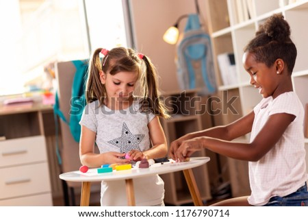 Two preschoolers playing with colorful plasticine and having fun. Focus on the girl on the left #1176790714