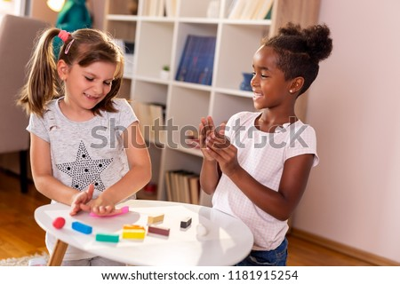 Two preschoolers playing with colorful plasticine and having fun. Focus on the girl on the right