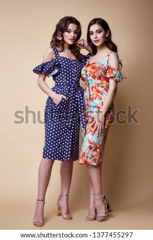 Two pretty beautiful sexy elegance woman skin tan body fashion model glamor pose wear trend dress casual clothes party summer collection makeup hair style brunette success accessory jewelry studio.