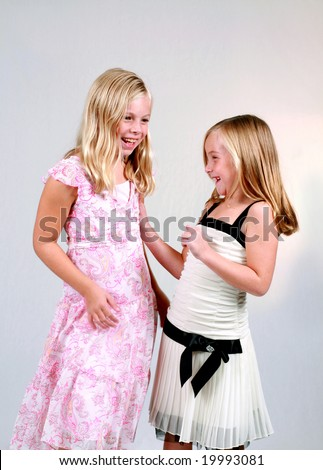 two pretty blonde preteen girls in dresses laughing - stock photo
