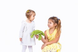 Two pretty blonde sisters posing in the beautiful dresses and two ponytails, elder sister holding in her hand a soft turtle toy and wants to give it to her younger sister.