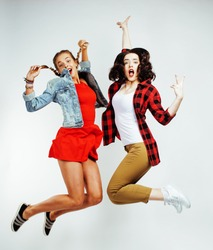 two pretty brunette and blonde teenage girl friends jumping happy smiling on white background, lifestyle people concept close up