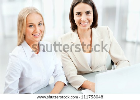 Two pretty business women working in the office