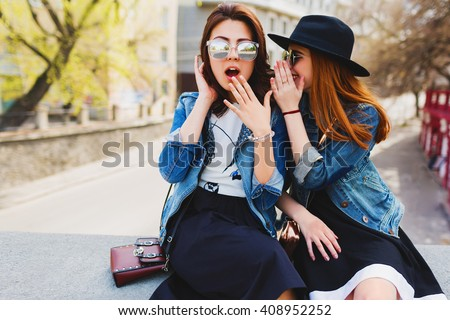 Two  pretty cuter teenagers  shares secrets, gossip. Surprise face, emotions,  Best friends wearing stylish outfit, black hat, sunglasses, dress. Bright spring  colors.