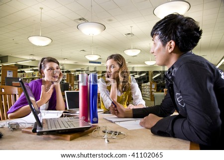Two pretty female college students studying with handsome male student in school library