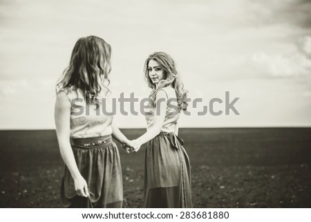 Two pretty girls holding hands in the field, sepia effect