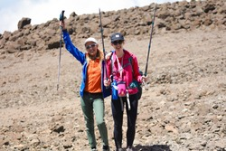 Two pretty girls in sport wear standing on the mountain with all equipment for the climbing. Rocks, no plants and trees. Dangerous and extreme adventure in Africa. Comfortable shoes, holding sticks