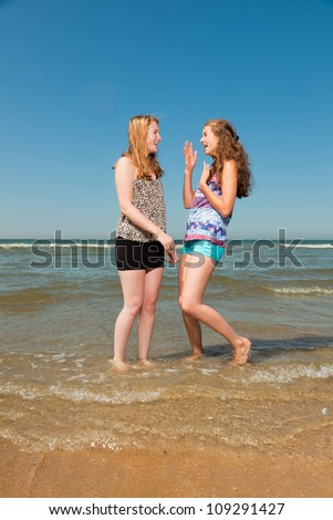 Two pretty girls playing and enjoying the refreshing on a hot summers day. Clear blue sky. Having fun on the beach.