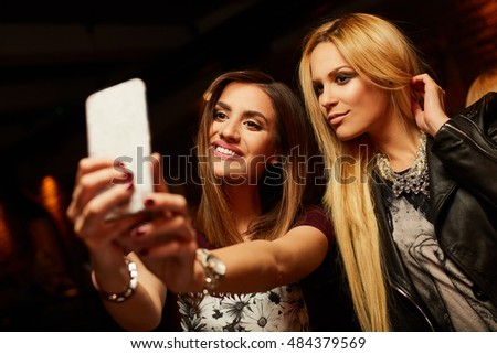 Two pretty girls take pictures at the club