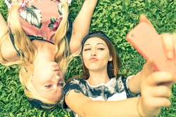 Two pretty girls taking a self portrait - Young women with a sportive casual outfit lying on meadow and having fun while taking a selfie