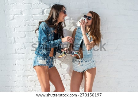 two pretty girls wearing sunglasses in summer jeanswear street urban casual style talking, laughing having fun on the background of brick wall