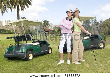 two pretty golf player with her golf cars