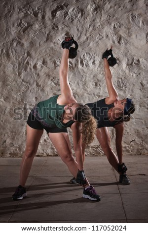 Two pretty ladies women lifting kettlebell weights over their shoulders